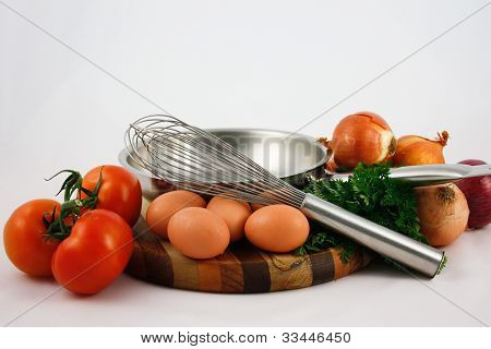 Frypan with eggs, tomatoes and onions and whisk