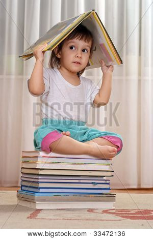Little Caucasian Baby Sitting On A Pile Of Books