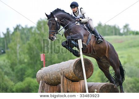 Eventer rider on horse overcomes obstacle