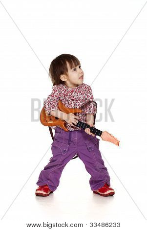 Beautiful Happy Little Caucasian Girl Plays With A Guitar