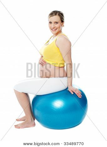 Relaxed Pregnant Woman Sitting On Pilate Ball