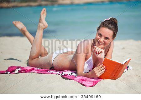Frau liest ein Buch am Strand