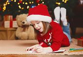Dreamy Little Girl In Red Xmas Hat Writing Letter To Santa Under Xmas Tree, Making Wishes On Christm poster