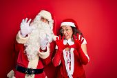 Middle age couple wearing Santa costume and glasses over isolated red background afraid and terrifie poster