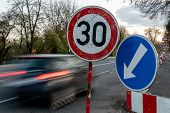 A Fast Driving Blue Speeding Car With Motion Blur Effect Near The Traffic Sign Limiting The Maximum  poster