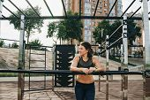 Attractive Fit Young Woman In Sport Wear Rest On The Street Workout Area. The Healthy Lifestyle In T poster
