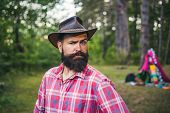 Guy In Forest. Handsome Bearded Male. Natural Background. Brutal Brunette Bearded Man In Hat On A Ba poster