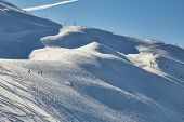 Ski slopes in the French Alpes, people skiing in the distance poster