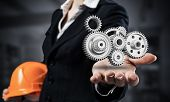 Businesswoman Holds In Palm 3d Gears Mechanism. Woman In Business Suit With Orange Safety Helmet. Co poster