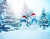 A happy family of snowmen standing in a winter landscape with Christmas trees. Background with snowm poster
