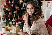 Christmas And New Year Concept - Young Beautiful Woman Sitting In Decorated Living Room With Gift Bo poster