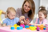 Nursery Kids Play With Educational Toys In Classroom. Kindergarten Teacher Looks After Children poster