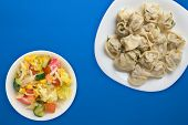 Dumplings On A White Plate On A Blue Background. Top View Of Dumplings With Vegetable Salad. Asian C poster