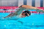 Swimmer man doing crawl swim in swimming pool portrait. Closeup of athlete wearing goggles, swimming poster