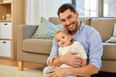 family, parenthood and fatherhood concept - father with little baby daughter at home poster