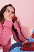 stock photo of snot  - portrait of a sick girl speaking at phone - JPG