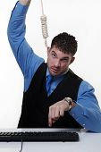 stock photo of hangmans noose  - man working at his desk with a hangmans noose around his neck - JPG