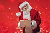 Jolly Santa Claus holds a gift box  over festive red background. The atmosphere of celebration and m poster