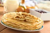 stock photo of crepes  - Fresh homemade crepes on plate with ingredients and strawberry jam in the back  - JPG