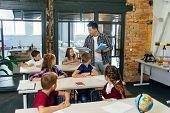 Teacher Of Elementary School Puts Notebooks On Desks Pupils For Learning. Group Of Schoolchildren Pr poster