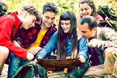 Hiking Group Of Happy Friends Looking At Map Sitting  In The  Forest Outdoors - Teenagers Excursion  poster