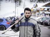Young Handsome Man In Sportswear Holding Ski On Shoulder And Looking At Camera poster
