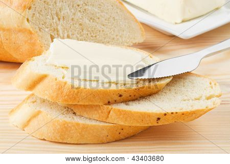 Slice Of Baguette With Butter On Wooden Bord