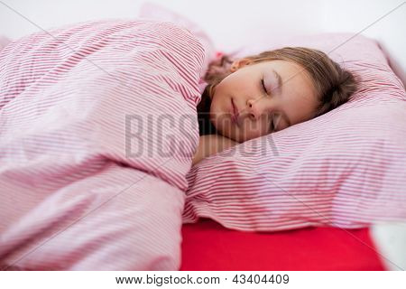 Portrait of a little girl sleeping on the bed in her bedroom