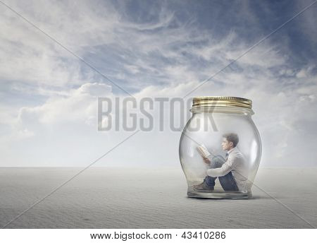 young boy reads book sitting in a jar in the desert