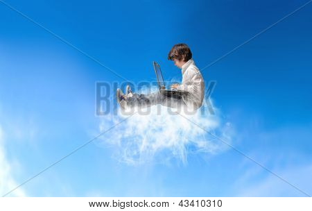 young boy with laptop sitting on a cloud in the sky