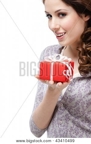 Enigmatic young woman hands a gift wrapped in red paper, isolated on white