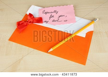 Note in envelope with pencil on wooden background