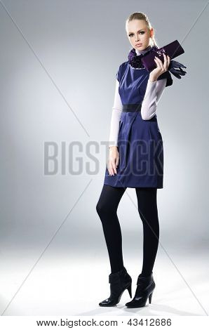 fashion model holding little purse posing on light background