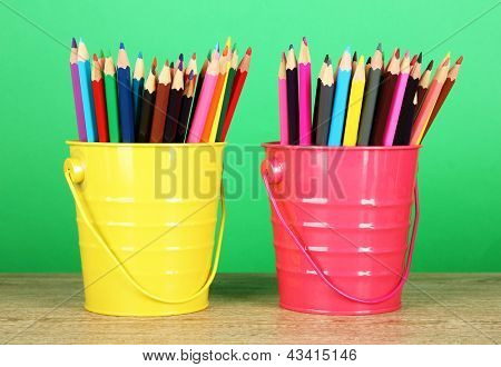 Colorful pencils in two pails on table on green background