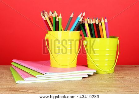Colorful pencils in two pails with copybooks on table on red background