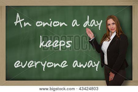 Teacher Showing An Onion A Day Keeps Everyone Away On Blackboard
