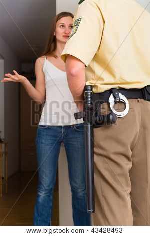 Police officer at front door of home interrogating a woman or witness regarding a police investigation