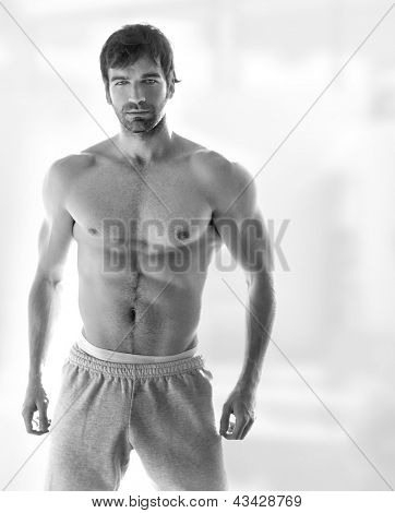 Sexy portrait of a very muscular hot shirtless male model in in sweatpants with copy space