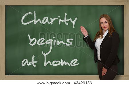 Teacher Showing Charity Begins At Home On Blackboard