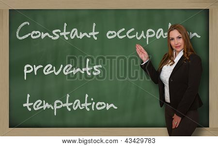 Teacher Showing Constant Occupation Prevents Temptation On Blackboard