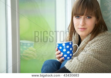 Young Woman Relaxing By Window With Cup Of Tea