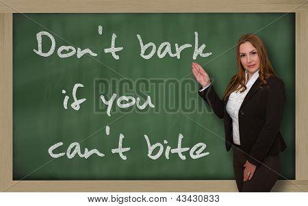 Teacher Showing Don't Bark If You Can't Bite On Blackboard