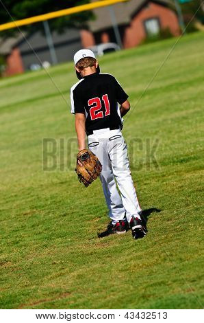 Youth Baseball Player Walking On Field