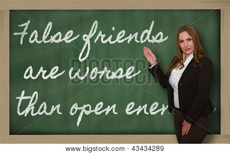 Teacher Showing False Friends Are Worse Than Open Enemies On Blackboard