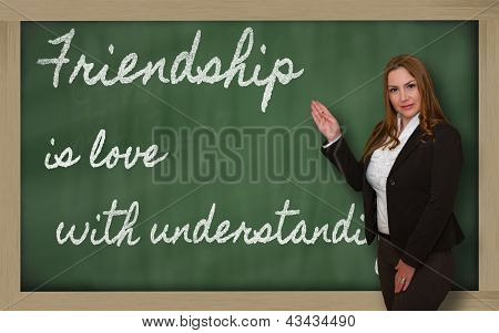 Teacher Showing Friendship Is Love With Understanding On Blackboard