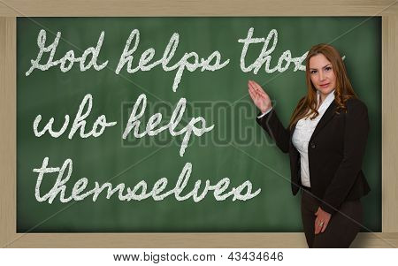 Teacher Showing God Helps Those Who Help Themselves On Blackboard