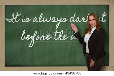 Teacher Showing It Is Always Darkest Before The Dawn On Blackboard