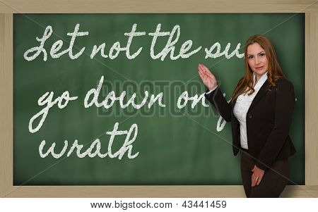 Teacher Showing Let Not The Sun Go Down On Your Wrath On Blackboard