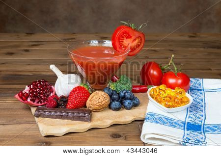 Wooden table and a small tray filled with antioxidants fruits and vegetables