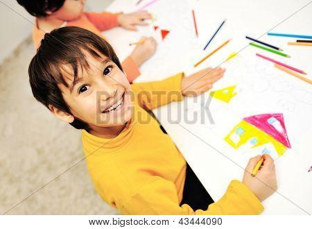 Zwei kleine Kinder am Tisch zeichnen mit Buntstiften